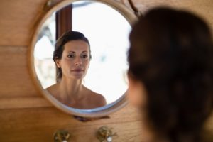 Woman looking at mirror in cottage